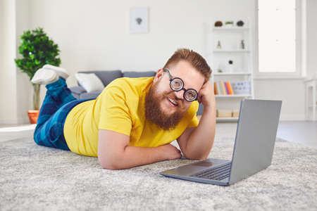 Work online at home office. Funny fat man in silly glasses works online communicates video chat call using laptop lying on the floor at home.