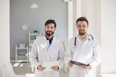 Two practicing doctors with clipboard standing in a clinic office.Health care medicine.Medical workers are waiting for patients at the workplace. Health care medicine. Practicing physician therapist on the background of a medical office.