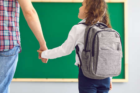 Little girl with backpack holding her father's hand at classroom. Back view of child with parent on first day at school. Primary education