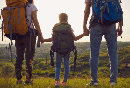 Happy family with backpacks on the nature at sunset. Hiking family tourism concept.Back view. A friendly family looks at the sunset on an adventure walk. 版權商用圖片