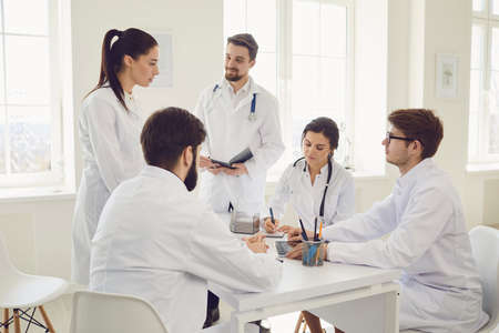 Group of practicing doctors in a meeting discuss the diagnosis of a patient sitting at desk in a clinic office. Confident doctors at the conference talking.