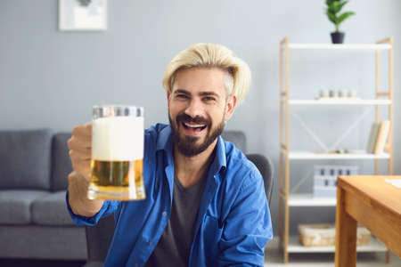 Cheerful young guy with beer talking to his male friends online from home, copy space. Handsome man celebrating with buddies on webcam