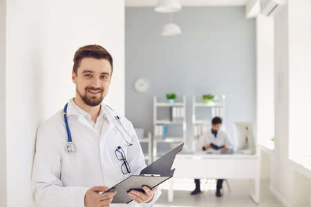 A male doctor with a stethoscope smiling a clipboard while standing in a clinic. Practicing physician therapist on the background of a medical office. Stock fotó