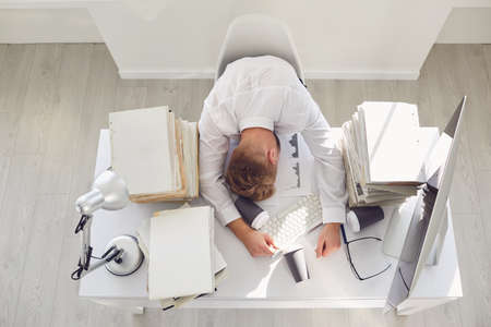 A lot of work in the office. Tired busy businessman sleeping at a table with a computer. Banque d'images - 151447642