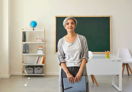 The teacher in the classroom. A woman with gray hair mature teacher with a notebook in her hand looks at the camera standing on the background of the class.