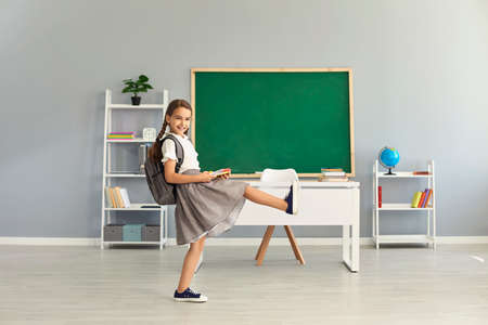 Cute girl in uniform with backpack walking in classroom, copy space text. Elementary pupil starting new school year. Primary education concept