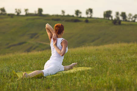 Anonymous female doing split and grasping hands behind back while practicing yoga in evening in countryside