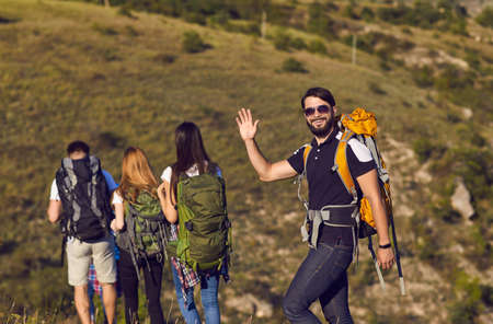 A group of hikers with backpacks are walking along the hill in the mountains in nature. Travel adventure people tourists.