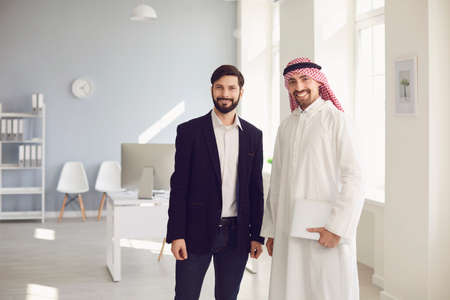 Arab and European business people are standing together in a modern office. Businessmen meeting contract conclusion market analysis investment concept. Stock fotó
