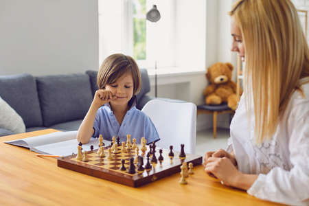 Family hobbies. Young mother playing chess with her son at home. Cute little boy engaged in board game with his parent in light room