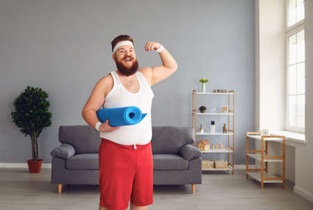 Funny fat man in sportswear shows muscles standing in the room at home.