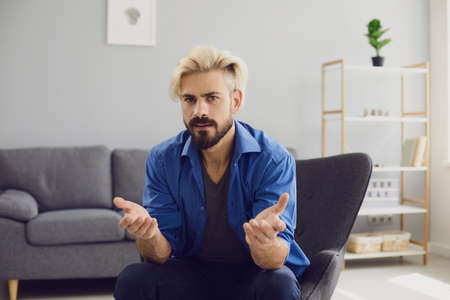 Puzzled adult bearded man in blue shirt and dyed hair sitting in cozy chair with open mouth and hands apart while looking at camera in light room