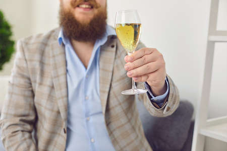 Online dating concept. Funny fat man with glass of wine having romantic talk to his girlfriend on webcam from home. Young guy speaking with his lover through internet 写真素材