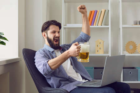Online TV. Young guy with mug of beer watching football in front of laptop at home. Sports fan cheering for his soccer team indoors