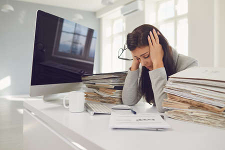 Woman brunette businesswoman in glasses with a mountain of documents on the table tired depressed emaciated disappointed depressive at the table in the office.