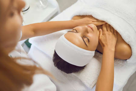 Hands of cosmetologist or masseur making massage of face, neck and upper shoulder girdle for serene young woman in beauty salon. Facial treatment, skincare, cosmetology concept Stock Photo