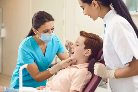Dentist and assistant check the teeth of a boy child in a dental clinic. Childrens orthodontist works at the workplace with a red-haired boy.