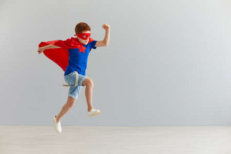 Happiness, freedom, childhood, movement and people concept, boy in red superhero cape and mask jump and fly.