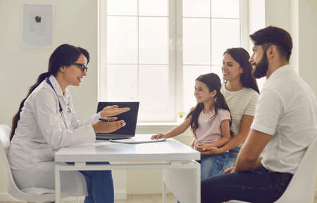 Family doctor. Young woman doctor consults parents with a little girl sitting at the table in the hospital.