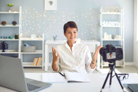 Positive female vlogger recording a video on camera sitting at desk in modern office. Happy businesswoman sharing experience making a pre-recorded webinar at home Imagens