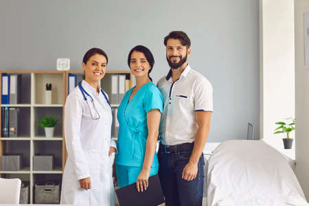 Young professionals at work. Group portrait of smiling multiracial medical workers together in hospital office. Friendly staff of modern clinic standing close to each other and looking at camera