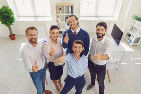 Good job. High angle of happy company employees giving thumbs-up smiling and looking at camera. Group of successful young business partners celebrating finding solution and win-win situation Foto de archivo