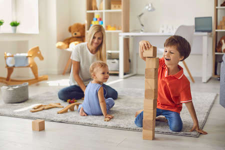 Happy young mother playing educational games and building wooden pyramid with smiling children on floor at home with room interior at background. Happy childhood and motherhood concept