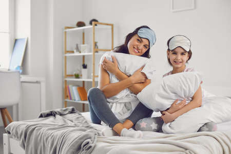 Smiling woman and girl wearing sleep masks and pajamas sitting on soft bed in cozy bedroom and hugging pillows while looking at camera Фото со стока - 155359784