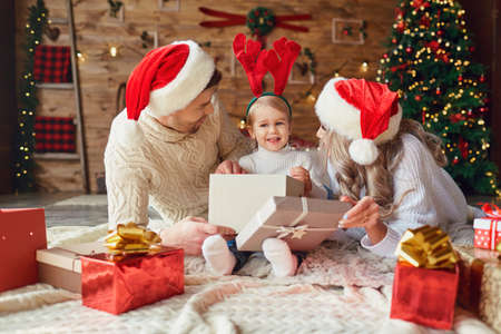 The family gives gifts to the child in the room with the Christmas tree. Фото со стока - 155359792