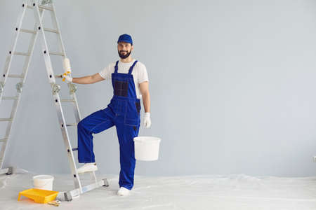 Young smiling professional worker in blue uniform standing with paint roller and bucket in hands near ladder and looking at camera in new apartment for repairing over grey walls background, copy space