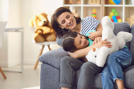 Happy young mother and smiling daughter relaxing together on sofa and playing with toy at home with room interior at background. Happy childhood and motherhood concept