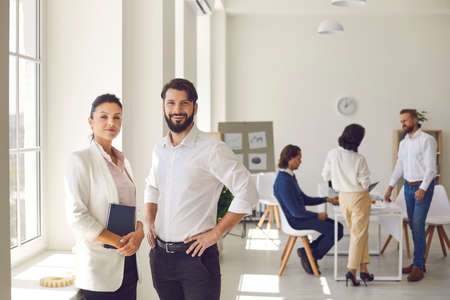 Young man and woman, 2 successful company co-founders, business partners or coworkers looking at camera. Confident female executive director and male manager standing in office after corporate meeting Фото со стока - 155359756