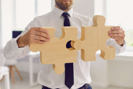 Cropped businessman or company manager joining 2 pieces of jigsaw puzzle. Metaphor for finding business solution or missing link, building strong business, implementing effective work methods Stock Photo