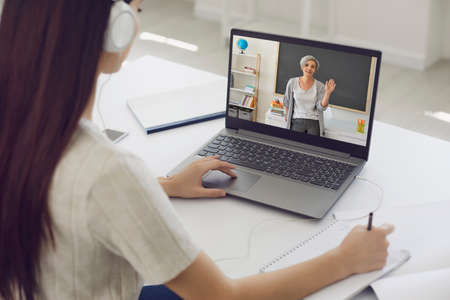Learning education course lecture online. Girl student in headphones listens to the teacher video chat application remotely at home.