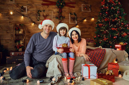 Parents in Santa hats with child with gifts on the bed in the room at Christmas. Фото со стока - 155383185