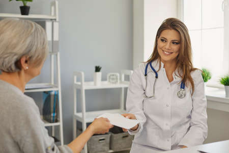 A friendly doctor is giving a prescription to a patient while sitting at the workplace in a medical clinic office. Medical consultation of a therapist at the hospital.