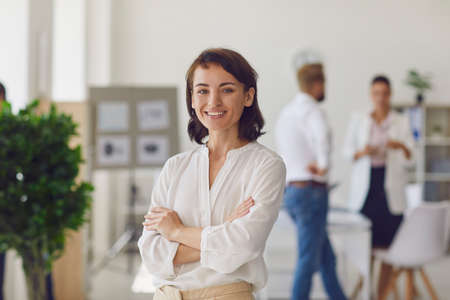 Portrait of happy successful woman in her workplace. Confident female company employee or department manager in office. Business lady in formal wear with arms folded looking at camera and smiling