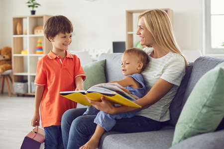 Happy young mother reading book to children sitting on comfortable couch in living room. Smiling nanny looking after toddler and preschool boys. Cheerful kids spending time with elder sister at home Foto de archivo