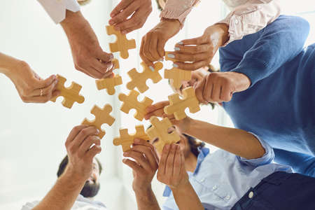 Cooperation and finding solution. From below of happy company employees playing game in team building meeting. Office workers joining parts of jigsaw puzzle as metaphor of unity and partnership