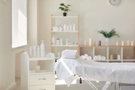 Newly opened massage room with all necessary supplies ready for professional body and skin treatment. Interior of modern beauty salon with spa table, fresh towels and skincare products. Copy space