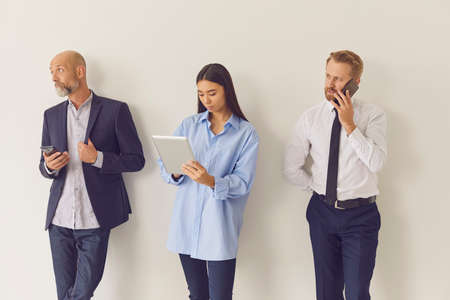 Business people use their gadgets to talk and view information on the Internet during work breaks. Skilled office workers stand on a gray wall background. Concept of teamwork and technology.