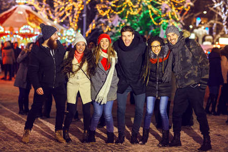 Group of excited men and women standing close together on market in Christmas time