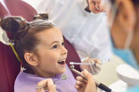 Little brave smiling little girl getting tooth cavity from dentist and assistant in dental clinic without fear. Dental care and visiting dentist concept