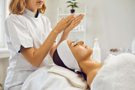 Woman dermatologist or therapist spreading moisturizing cream on hands ready to apply on young womans face after skincare treatment or massage in beauty wellness salon, side view Фото со стока