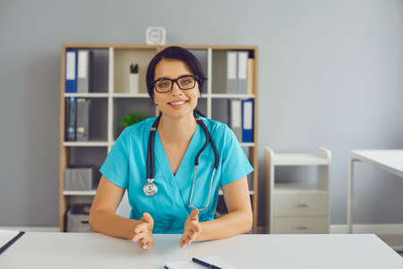 Friendly doctor at desk looking at camera and providing consultation to patient during video call. General practitioner in hospital office talking to client or making professional vlog or webinar