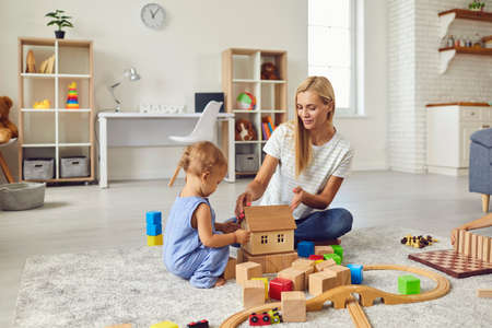 Mom and child at home. Young mother playing with little son teaching him to build toy house. Happy nanny engaging toddler boy in fun activities with wood blocks on warm floor in cozy studio apartment