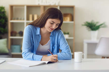 Young smiling woman studying and writing down notes during online lesson on laptop at home. Online education and learningin internet concept