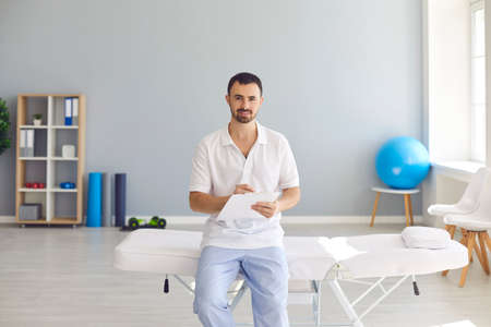 Male massagist with clipboard in massage room of new clinic. Professional doctor, physiotherapist, licensed chiropractor, manual therapist, general practitioner or rheumatologist in hospital office 免版税图像