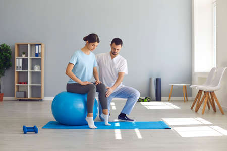 Man doctor chiropractor or osteopath fixing woman on fitness ball in right position for pain relief during visit in manual therapy clinic. Professional chiropractor during work and pain relief concept Banque d'images