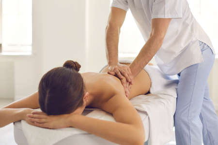Woman getting medical back massage done by professional massagist or physiotherapist in modern health center. Masseur helping female patient reduce backache and cure other problems